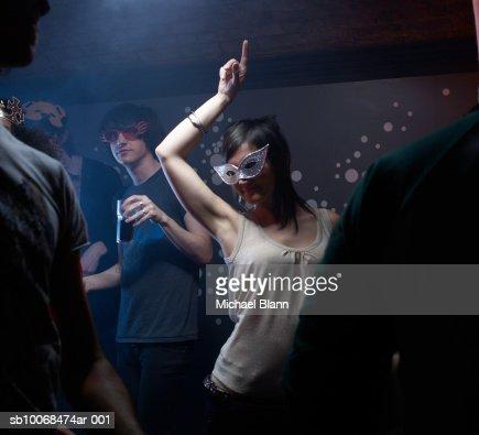 People wearing masks, dancing in night club : Stock Photo