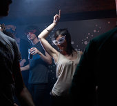 People wearing masks, dancing in night club