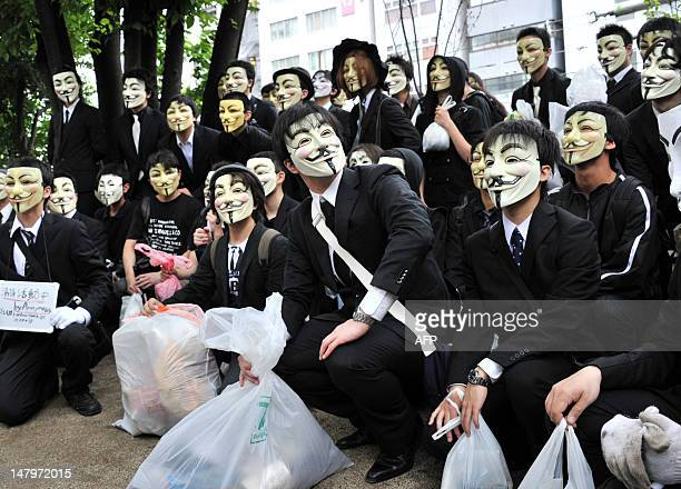 People wearing masks gather in a park after picking up litter as part of a clean up mission organised by hacker collective Anonymous on a street in...