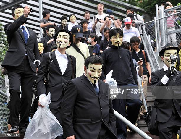 People wearing masks leave a park after picking up litter as part of a clean up mission organised by hacker collective Anonymous on a street in Tokyo...