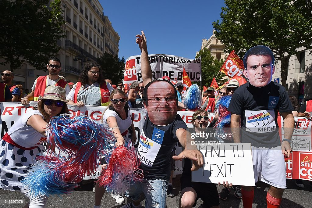 People wearing masks mocking French President Francois Hollande (C) and French Prime minister Manuel Valls (R) take part in a demonstration against the French government's planned labour law reforms, on June 28, 2016 in Marseille, southern France. Unions have called repeated strikes and marches in opposition to the law, which seeks to bring down France's intractable 10-percent unemployment rate by making it easier to hire and fire workers. / AFP / BORIS