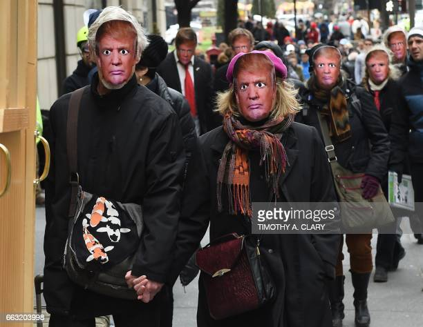TOPSHOT People wearing masks of US President Donald Trump take part in the 32nd Annual April Fools Day Parade in New York on April 1 2017 The theme...