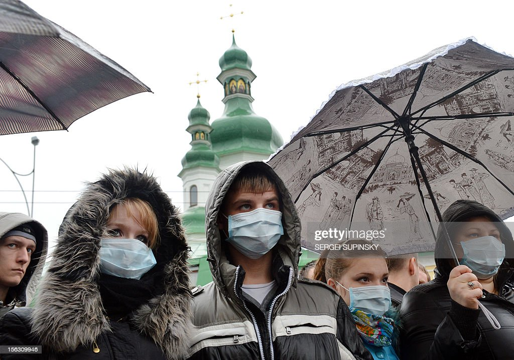 People wearing medical masks gather at the memorial monument to AIDS victims in Kiev during a rally called 'Ukraine to quarantine!' on November 13, 2012. Some 50 infected and sick people with AIDS, tuberculosis and hepatitis demand an increase of the financing of painful illness treatment.