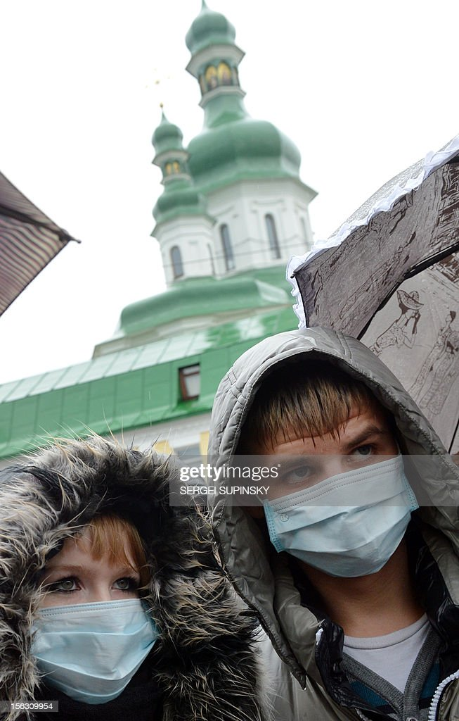 People wearing medical masks gather at the memorial monument to AIDS victims in Kiev during a rally called 'Ukraine to quarantine!' on November 13, 2012. Some 50 infected and sick people with AIDS, tuberculosis and hepatitis demand an increase of the financing of painful illness treatment. AFP PHOTO / SERGEI SUPINSKY