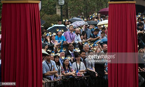People wearing Mickey Mouse ears watch the opening ceremony of the Shanghai Disney Resort in Shanghai on June 16 2016 Entertainment giant Disney...