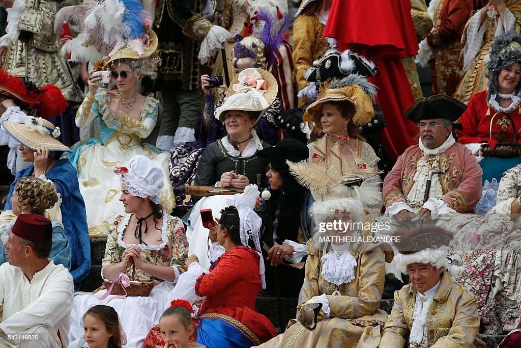 People wearing period costumes pose at the Chateau de Vaux-le-Vicomte (Vaux-le-Vicomte castle) in Maincy near Paris on June 26, 2016, during the annual Grand Siecle day event, a rendez-vous for costume passionates. / AFP / MATTHIEU