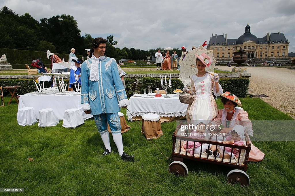 People wearing period costumes take part in a picnic in the gardens of the Chateau de Vaux-le-Vicomte (Vaux-le-Vicomte castle) in Maincy near Paris on June 26, 2016, during the annual Grand Siecle day event, a rendez-vous for costume passionates. / AFP / MATTHIEU