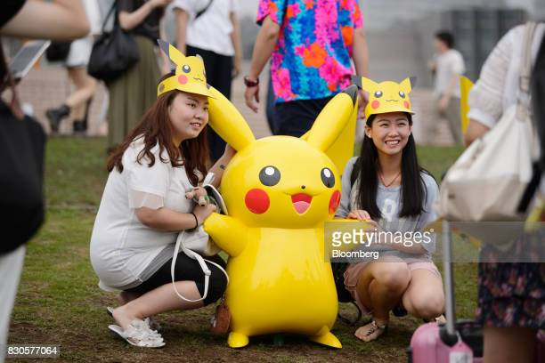 People wearing Pikachu paper visors pose for photographs with statues of the Pikachu character from Nintendo Co's Pokemon franchise during a Pikachu...