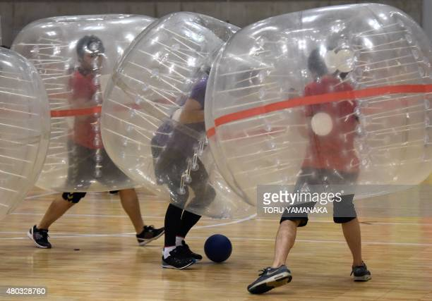 People wearing plastic made bubble balls enjoy a fiveonfive game of bubblesoccer in the sports festival of Japan's game maker Bandai Namco...