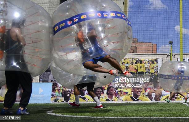 People wearing plastic made bubble balls enjoy a fiveonfive game of bubblesoccer in Medellin Antioquia department Colombia on October 10 2015 The...