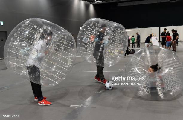 People wearing plastic made bubble balls enjoy a threeonthree game of bubblesoccer at the National Museum of Emerging Science and Innovation in Tokyo...