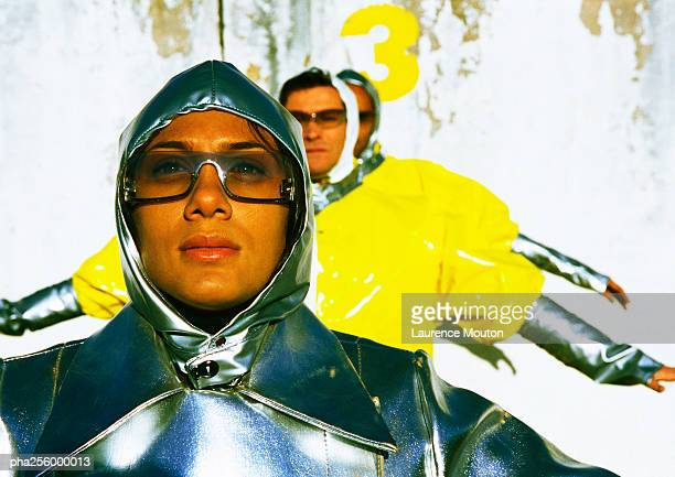 People wearing protective suits, arms at sides