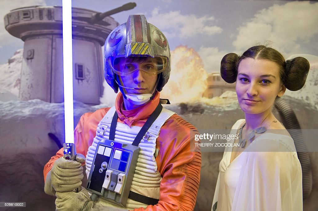 People wearing respectively a Luke Skywalker costume (L) and a princess Leia costume take part in a Star Wars convention in Cusset, on May 1, 2016. / AFP / Thierry Zoccolan