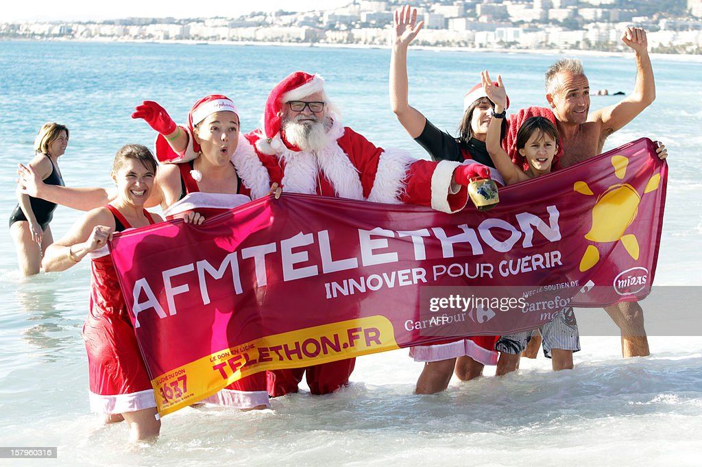 People wearing Santa Claus costumes and beachgoers hold a French charity operation Telethon banner as they stand in the Mediterranean Sea on December 8, 2012, in Nice, southern France.