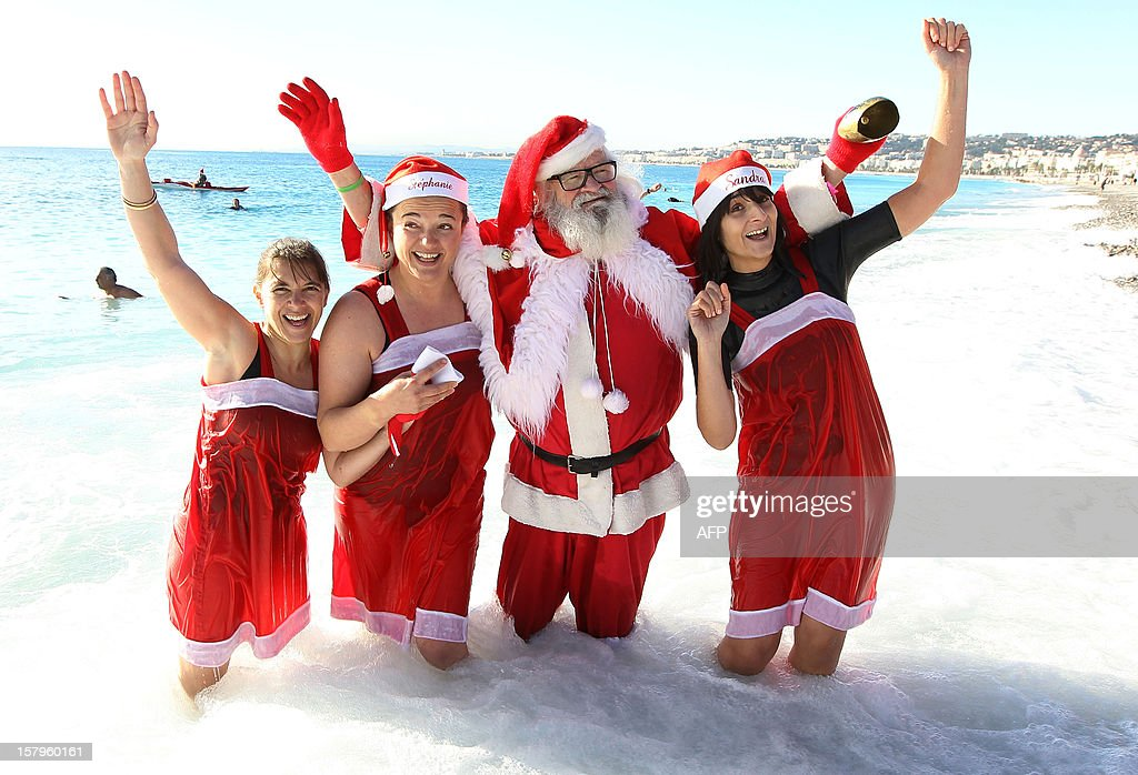 People wearing Santa Claus costumes pose for photo as they stand in the Mediterranean Sea on December 8, 2012 in Nice, southern France.