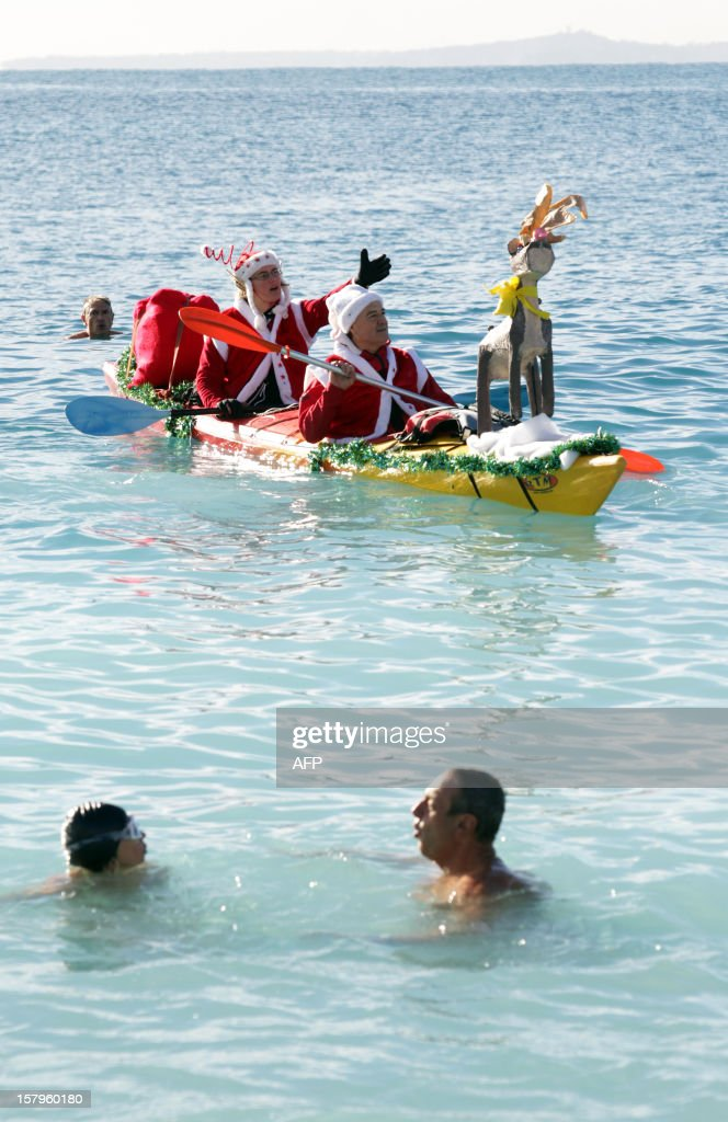 People wearing Santa Claus costumes ride a kayak in the Mediterranean Sea on December 8, 2012 in Nice, southern France.
