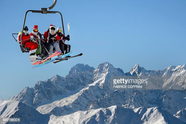People wearing Santa Claus costumes ride a ski lift on December 6 2015 above Verbier Swiss Alps The ski resort gave a free day pass to every skier...