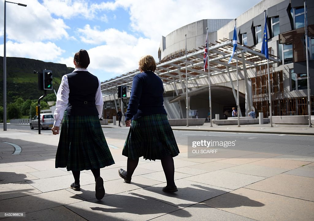 People wearing tartan kilts pass a Scottish Saltire (C), a Union flag (L), and a European Union (EU) flag as they fly in front of the Scottish Parliament building in Edinburgh, Scotland on June 27, 2016. British leaders battled to calm markets and the country Monday after its shock vote to leave the EU, while insisting London would be not rushed into a quick divorce. Britain's historic decision to be the first country to leave the 28-nation bloc has fuelled fears of a break-up of the United Kingdom with Scotland eyeing a new independence poll, and created turmoil in the opposition Labour party where leader Jeremy Corbyn is battling an all-out revolt. / AFP / OLI