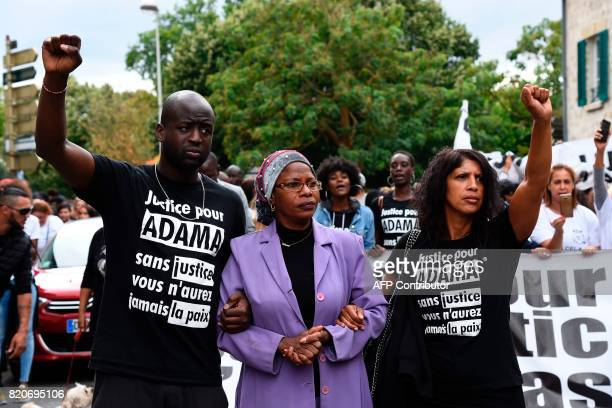 People wearing teeshirts reading 'Justice for Adama without justice you won't have peace' as they raise their fists during a march in memory of Adama...