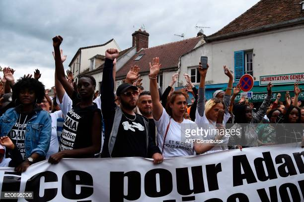 People wearing teeshirts reading 'Justice for Adama without justice you won't have peace' take part in a march in memory of Adama Traore who died...