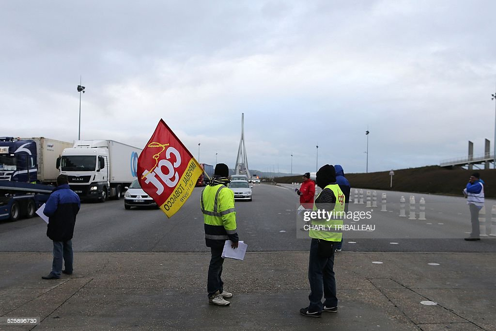 People wearing waistcoats and holding flags of the French CGT Trade Union distribute flyers as they block the road at a toll booth on the Normandy Bridge in Le Havre, northwestern France, on April 29, 2016 during a demonstration against the new labour draft-law. / AFP / CHARLY