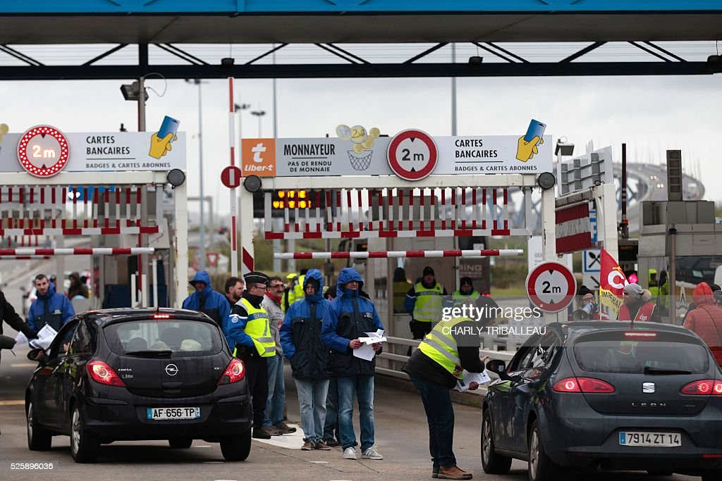 People wearing waistcoats of the French CGT Trade Union distribute flyers as they block the road at a toll booth on the Normandy Bridge in Le Havre, northwestern France, on April 29, 2016 during a demonstration against the new labour draft-law. / AFP / CHARLY