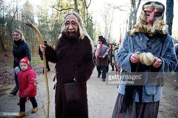 People wearring Martini mask parade as part of the traditional St Martin's celebration day at the Latvian Ethnographic Open Air Museum in Riga on...