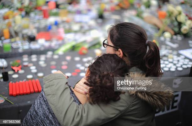 People weep as they gather to observe a minutesilence at the Place de la Republique in memory of the victims of the Paris terror attacks last Friday...