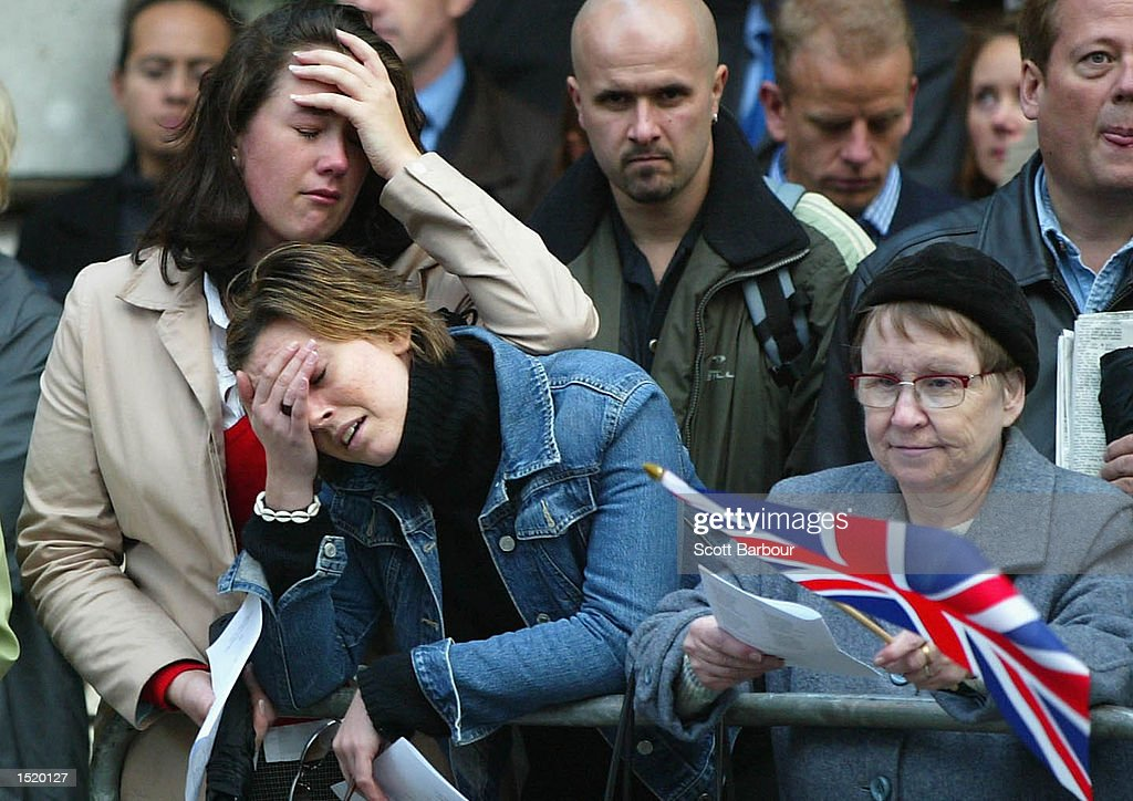People weep outside a remembrance service for the victims of the Bali bombing held at St Paul's Cathedral October 25, 2002 in London. The service was held to remember the almost 200 people killed on the Indonesian island of Bali October 12. Eleven Britons are confirmed dead with another eight presumed dead and 13 people still missing. About 2,000 people, including some family and friends of the victims attended.