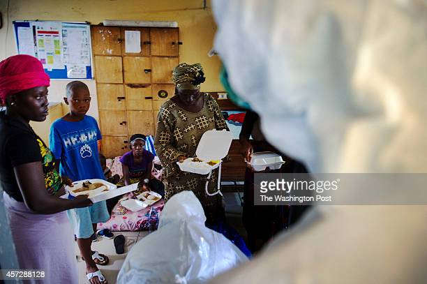 People who are able to walk receive lunch at Redemption Hospital which has become a transfer and holding center to an intake suspected Ebola patients...