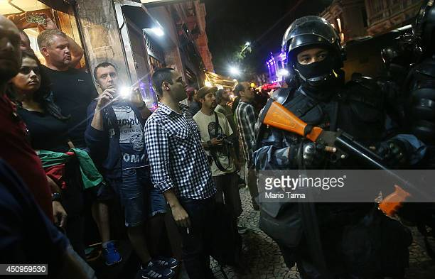 People who had been gathered in a bar watching a World Cup match look on as military police officers respond to a nearby protest on June 20 2014 in...
