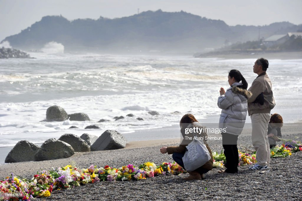 People who lost their families and friends by the tsunami followed by the strong earthquake, offer flower bunches at the Hisanohama coast on March 11, 2012 in Iwaki, Fukushima, Japan. Japan marks the first anniversary of the Great East Japan Earthquake.