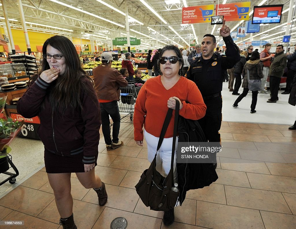 People who support Walmart workers protesting working conditions at the company inside a Walmart Superstore are asked to leave by a security officer (R) on November 23, 2012 in Secaucus, New Jersey. Unhappy Walmart employees are protesting across the US, seeking to make their demands for better pay and benefits more visible to the Americans flocking to the Black Friday shopping frenzy. AFP PHOTO/Stan HONDA