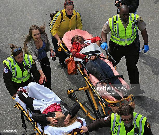 People who were injured in an explosion near the finish line of the 117th Boston Marathon are taken away from the scene on stretchers Krystara...