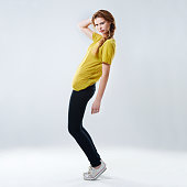 Full-length studio shot of a beautiful young woman posing in casual wear against a gray background