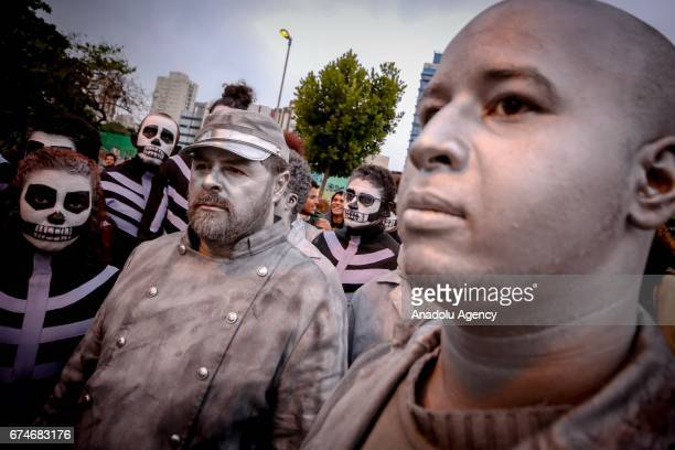 People with a mortuary mask attend demonstration on Largo da Batata in Sao Paulo Brazil on April 28 2017 A nationwide general strike has been called...