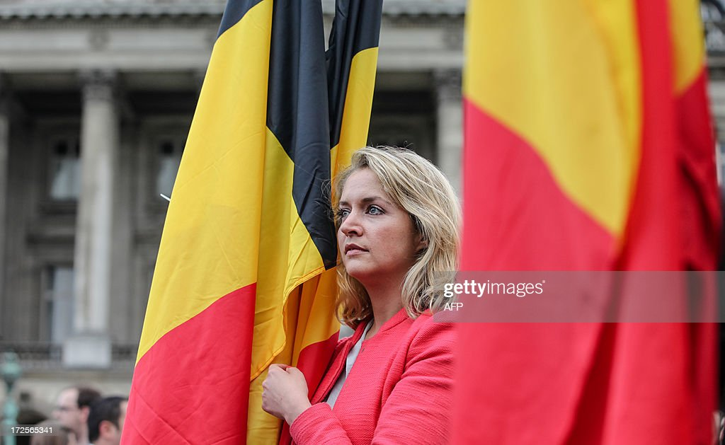People with Belgian flags stand in front of the royal palace at the Paleizenplein - Place des Palais in Brussels, on July 3, 2013. Today King Albert II of Belgium announced to the Belgian people his abdiction from the throne on 21 July. VIN