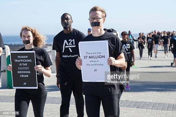 People with black tape on their mouth walk along the Sea Point coast as they attend a protest against human trafficking in Cape Town South Africa on...