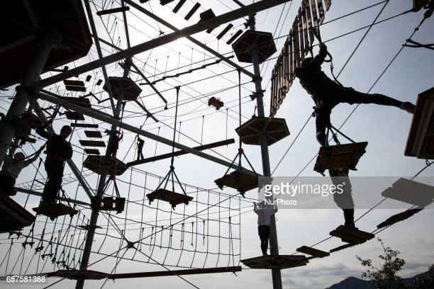 People with body harness try on the newly open athletic climbing attraction in Sagamiko Resort Pleasure Forest in Kanagawa prefecture Japan on March...