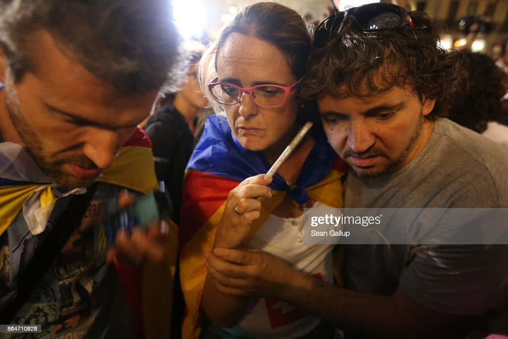 People with Catalan independence flags strain to hear a 9pm statement by Catalan regional president Carles Puigdemont on their smartphones while they gather in front of the Palau de la Generalitat de Catalunya, the building that houses the Catalonian presidency, following a demonstration for Catalan independence to demand the release of imprisoned Catalan leaders Jordi Sanchez and Jordi Cuixart on October 21, 2017 in Barcelona, Spain. The Spanish government announced measures today it will implement in triggering Article 155, which would lead to the imposition of direct rule by Spanish authorities in Catalonia and at least temporarily suspend the region's autonomy. The government also plans to hold Catalan regional elections in January. The moves come after Catalan regional President Carles Puigdemont let a Thursday deadline today pass and threatened to go forward with Catalan independence.