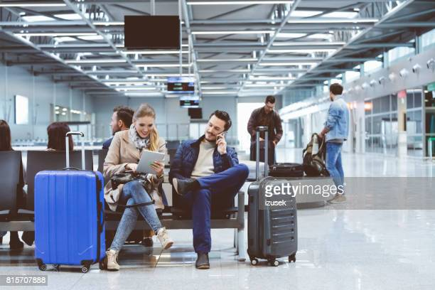 People with digital tablet and phone waiting at airport lounge