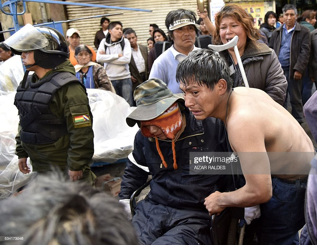People with disabilities are prevented by the riot police from reaching the presidential palace in La Paz to protest in demand of a raise in the subsidy for the disabled, on May 25, 2016. People with disabilities have been staging protests for almost a month demanding the government of Bolivian President Evo Morales that their benefit -- currently at 80 Bolivian pesos (about 11 US dollars) -- is raised to 500 pesos (about 72 US dollars). / AFP / AIZAR