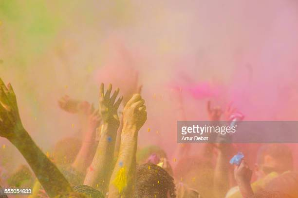 People with hands up throwing Holi colorful powder