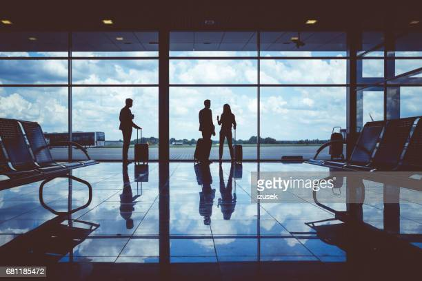 People with luggage waiting at airport lounge