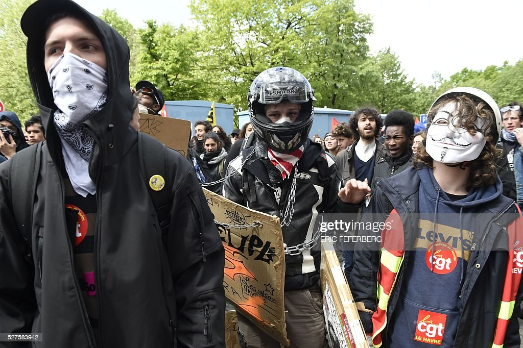 People with masks gather during a demonstration against the government's planned labour law reforms on May 3, 2016, in Paris as French lawmakers begin to examine the contested labour reform bill at the Parliament. Unions fear it will erode the cherished rights of workers on full-time contracts, while student organisations -- who have been at the forefront of the protests -- believe it will fail to create 'real' jobs for young people.
