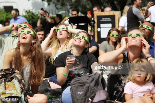 People with protective glasses distributed by Google Inc observe a total solar eclipse in New York on Aug 21 2017 Google revealed its newest mobile...