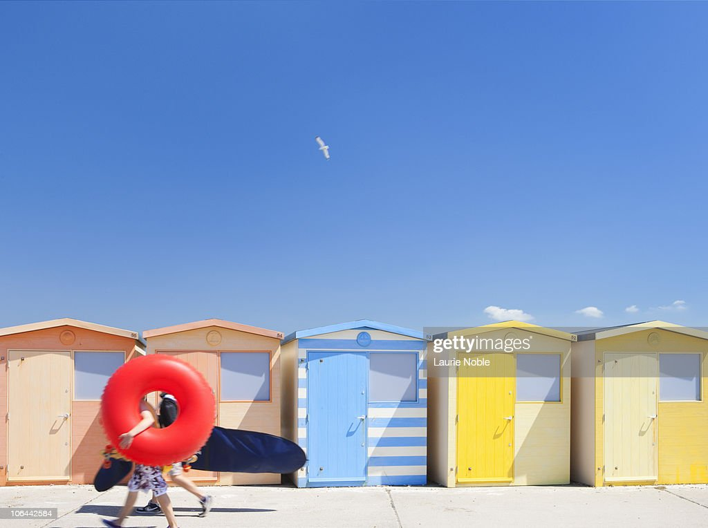People with Ring and Surf Board walking past Huts : Stock Photo