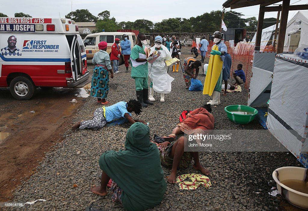 People with suspected Ebola virus lie on the ground after arriving by ambulance and just before being admitted to the Doctors Without Borders Ebola...
