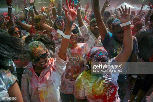 People with their faces covered in coloured powder react as more powder is thrown during Holi festivals at a temple on March 26 2016 in Kuala Lumpur...