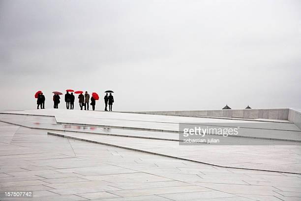 Menschen mit Sonnenschirmen-moderne gepflasterten square auf der Vorderseite